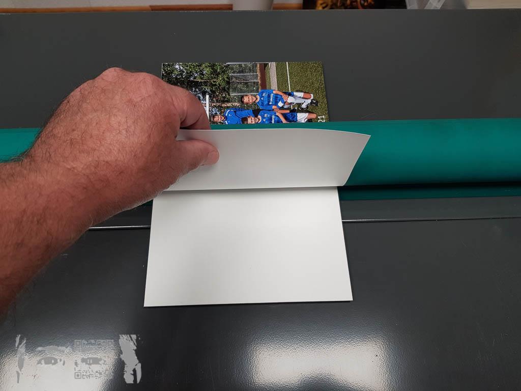Mit der Aufziehwlaze gelingt das blasenfreie Andrücken auf die vom Deckpapier befreite Aufziehfolie zuverlässiger. Selbst kleine Partikel, die unter das Foto geraten, können sich durchdrücken.